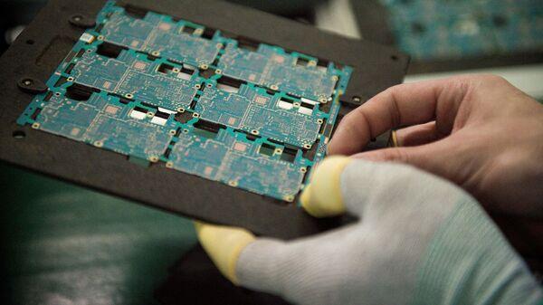 Sơ đồ các thành phần trong chip điện thoại thông minh được công nhân xử lý tại nhà máy Oppo ở Đông Quan, Trung Quốc. - Sputnik Việt Nam