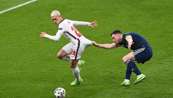 Cầu thủ bóng đá Anh Phil Foden đang tranh bóng với Andrew Robertson người Scotland trong trận đấu bảng D UEFA EURO 2020 giữa Anh và Scotland - Sputnik Việt Nam