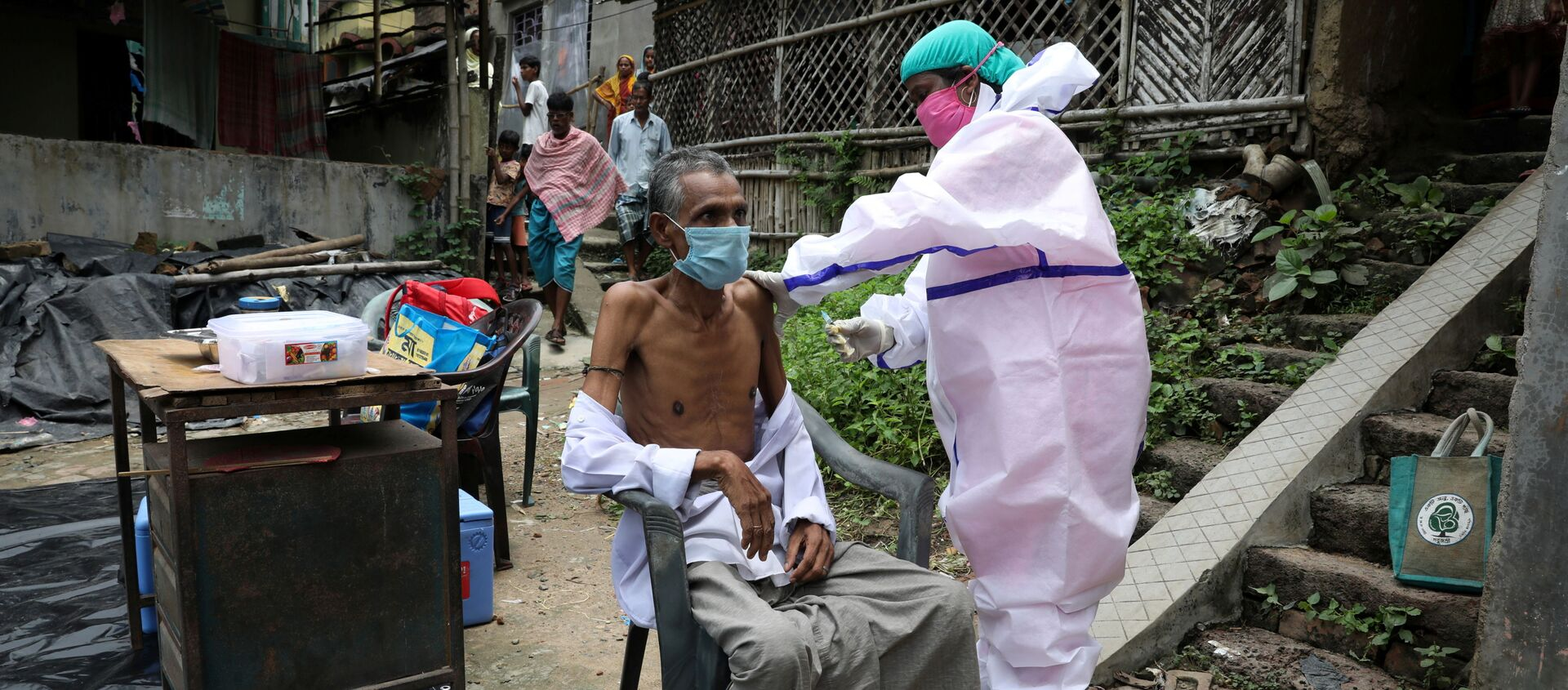 Motiar Rahman, một người dân trong làng, nhận một liều vắc-xin COVISHIELD, vắc-xin phòng bệnh do coronavirus (COVID-19) do Viện Huyết thanh của Ấn Độ sản xuất, trong một đợt tiêm chủng và thử nghiệm tận nhà tại Đảo Uttar Batora ở quận Howrah ở Tây Bengal bang, Ấn Độ, ngày 21 tháng 6 năm 2021. - Sputnik Việt Nam, 1920, 24.06.2021