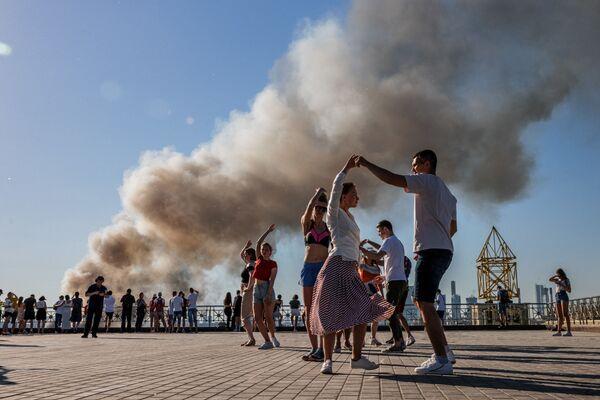 Cặp đôi nhảy vũ điệu samba trong nền khói bốc lên từ đám cháy kho pháo hoa ở Matxcơva  - Sputnik Việt Nam