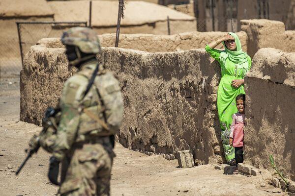 Lính Mỹ đứng cạnh một phụ nữ và em bé cư dân địa phương trong cuộc tuần tra của quân đội Mỹ ở Rumailan - Sputnik Việt Nam