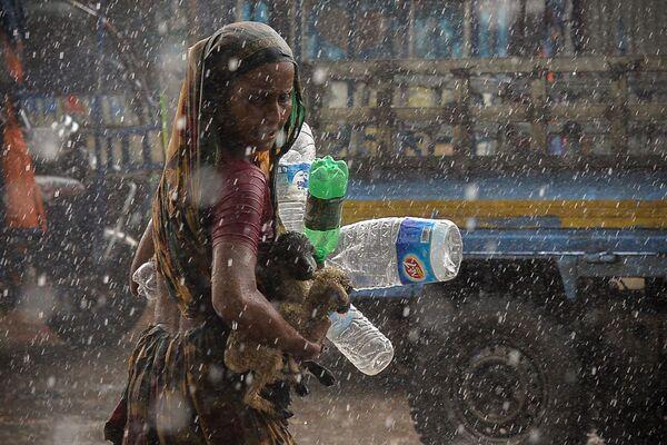 Người phụ nữ tìm nơi trú chân trong lúc có mưa bão ở Dhaka - Sputnik Việt Nam
