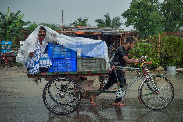 Một người đàn ông ngồi tránh mưa trên xe kéo trong trận mưa bão ở Dhaka - Sputnik Việt Nam