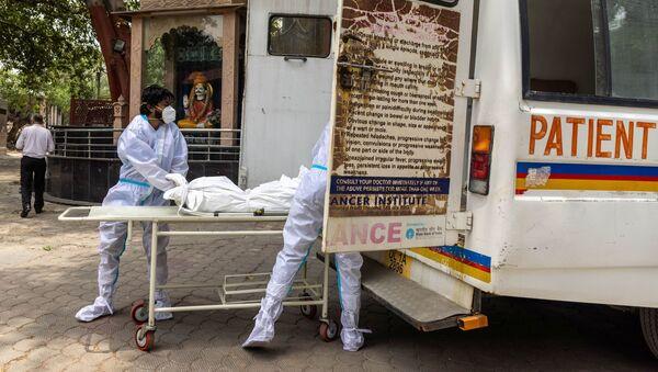 Các bác sĩ đưa xác một người chết vì coronavirus vào ô tô. - Sputnik Việt Nam