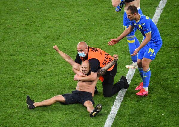 Nhân viên an ninh với một người đàn ông chạy vào sân trong trận Thụy Điển-Ukraina tại UEFA EURO 2020 - Sputnik Việt Nam