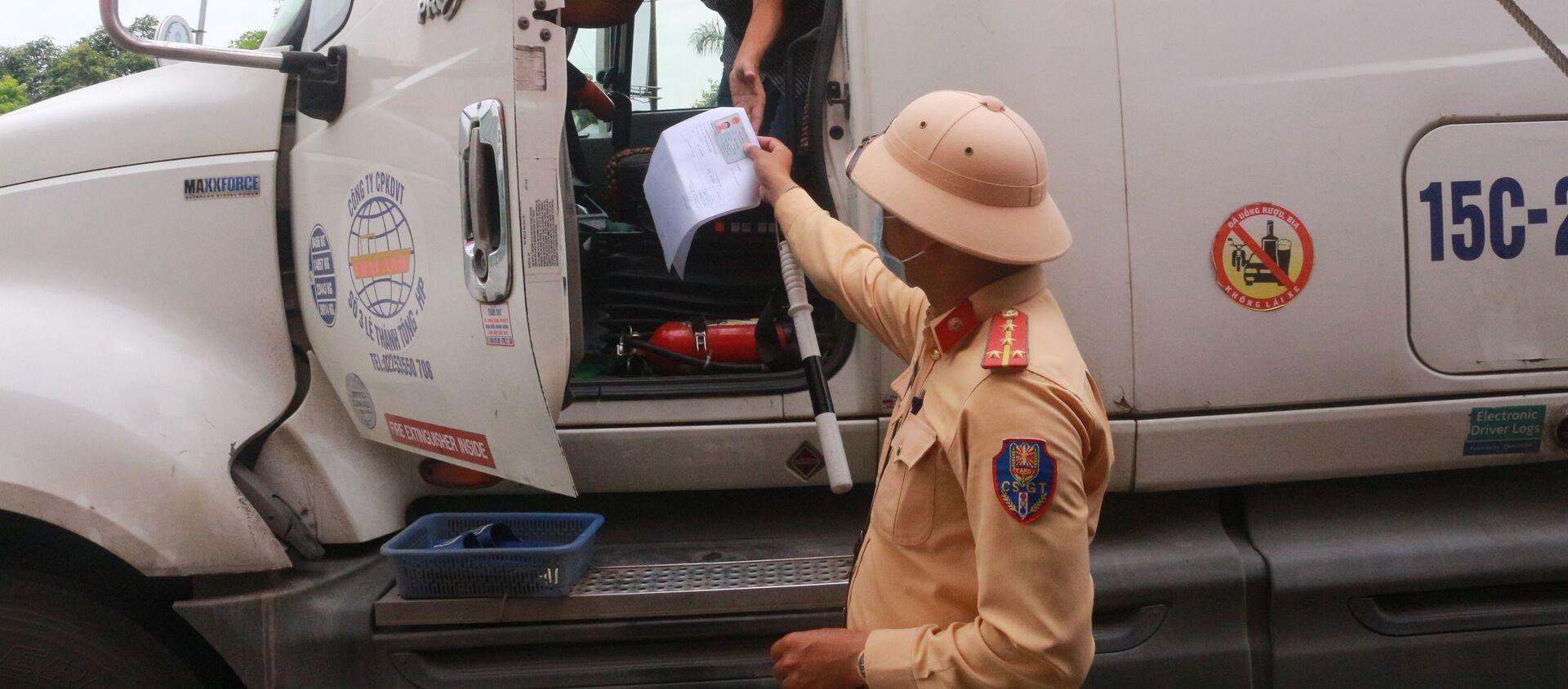 Cảnh sát giao thông công an thành phố Uông Bí (Quảng Ninh) kiểm tra các thủ tục của lái xe container trước khi qua chốt cầu Đá Bạc - Sputnik Việt Nam, 1920, 02.07.2021
