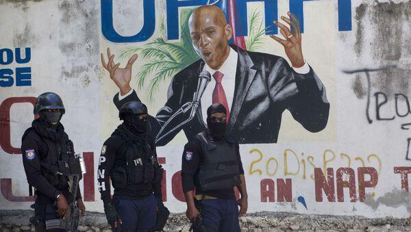 Cảnh sát đứng gần bức tranh tường có hình Tổng thống Haiti Jovenel Moise, gần tư dinh của nhà lãnh đạo nơi ông bị giết bởi các tay súng vào sáng sớm ở Port-au-Prince, Haiti, Thứ Tư, ngày 7 tháng 7 năm 2021. - Sputnik Việt Nam