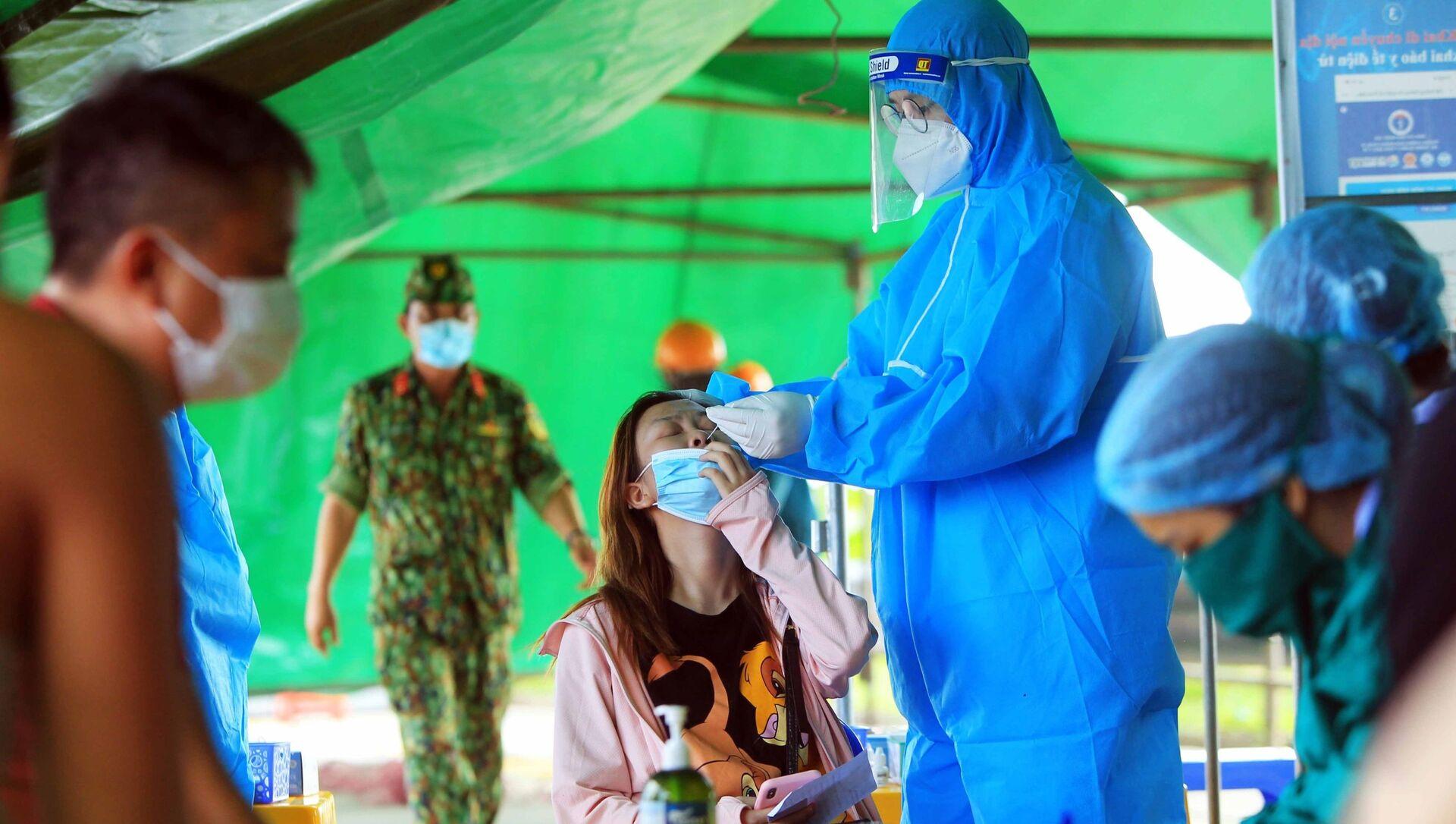 Lực lượng y bác sĩ lấy mẫu xét nghiệm Covid-19 cho các chủ phương tiện và những hành khách tại các điểm chốt . - Sputnik Việt Nam, 1920, 09.07.2021
