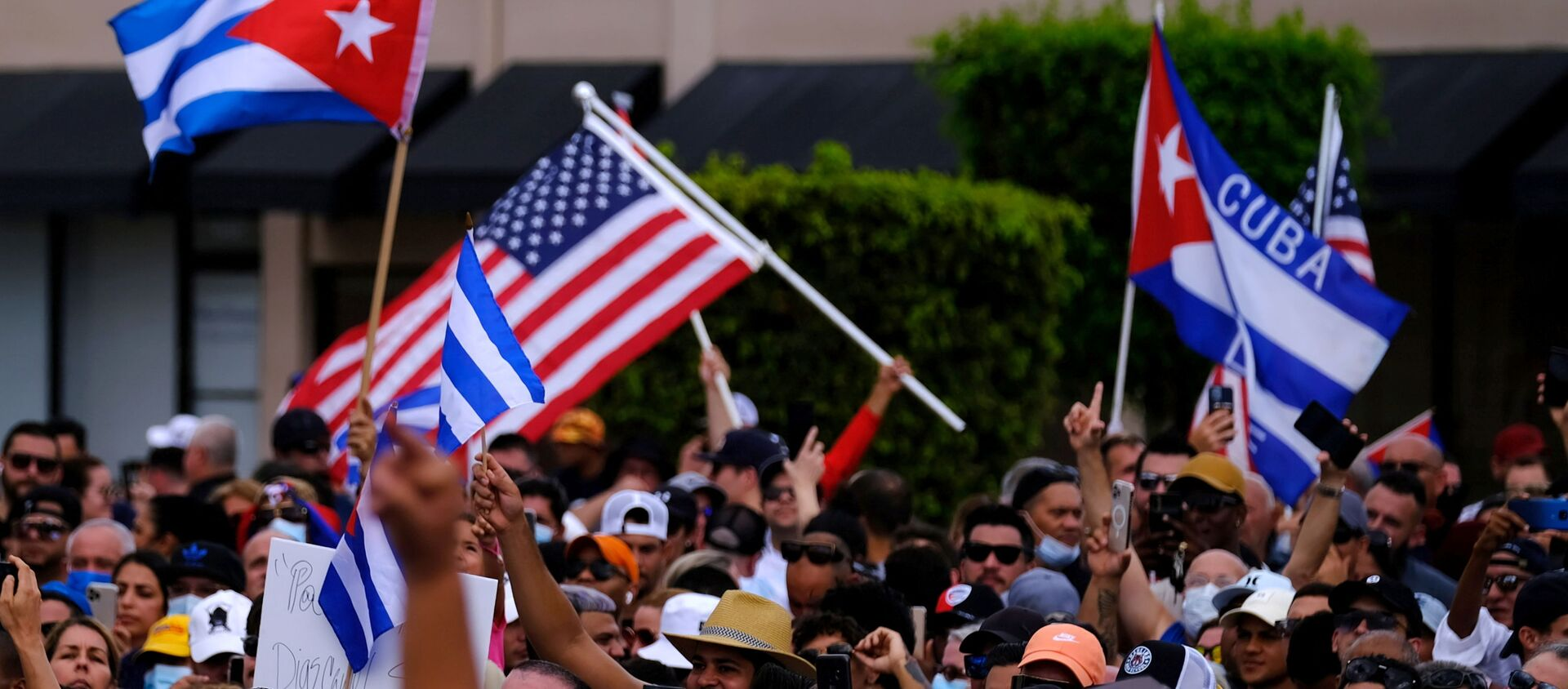 Emigres in Little Havana wave American and Cuban flags as they react to reports of protests in Cuba against the deteriorating economy, in Miami, Florida, U.S., July 11, 2021 - Sputnik Việt Nam, 1920, 15.07.2021