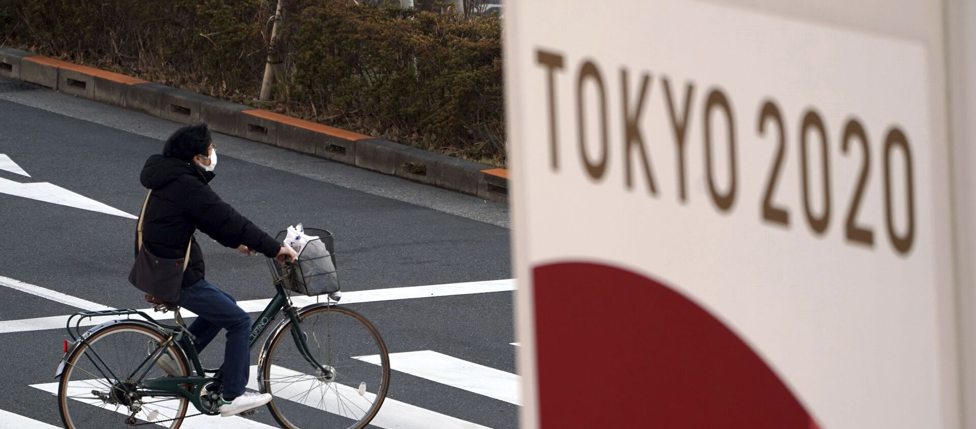 Một người đi xe đạp đeo khẩu trang bảo vệ trên nền biểu ngữ Thế vận hội Tokyo 2020 - Sputnik Việt Nam, 1920, 21.07.2021