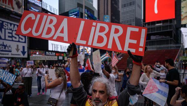 Người biểu tình cầm biểu ngữ trong một cuộc mít tinh được tổ chức đoàn kết với các cuộc biểu tình chống chính phủ ở Cuba, tại Quảng trường Thời đại, New York vào ngày 13 tháng 7 năm 2021. - Một người chết và hơn 100 người khác, bao gồm các nhà báo độc lập và nhà bất đồng chính kiến, đã bị bắt sau khi chưa từng có tiền lệ Các nhà quan sát và các nhà hoạt động cho biết các cuộc biểu tình chống chính phủ ở Cuba, với một số người còn lại bị giam giữ hôm thứ Ba. - Sputnik Việt Nam