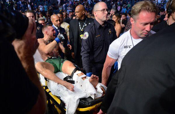 Võ sĩ Ireland Conor McGregor trên cáng sau trận tỷ thí với đối thủ Mỹ Dustin Poirier - Sputnik Việt Nam