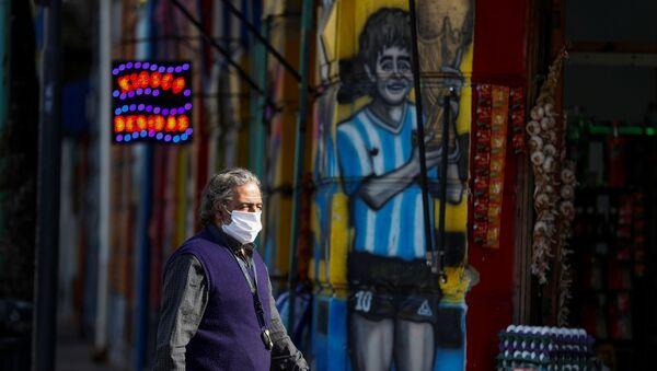 Người đàn ông đi qua bức vẽ graffiti mô tả Diego Maradona - Sputnik Việt Nam