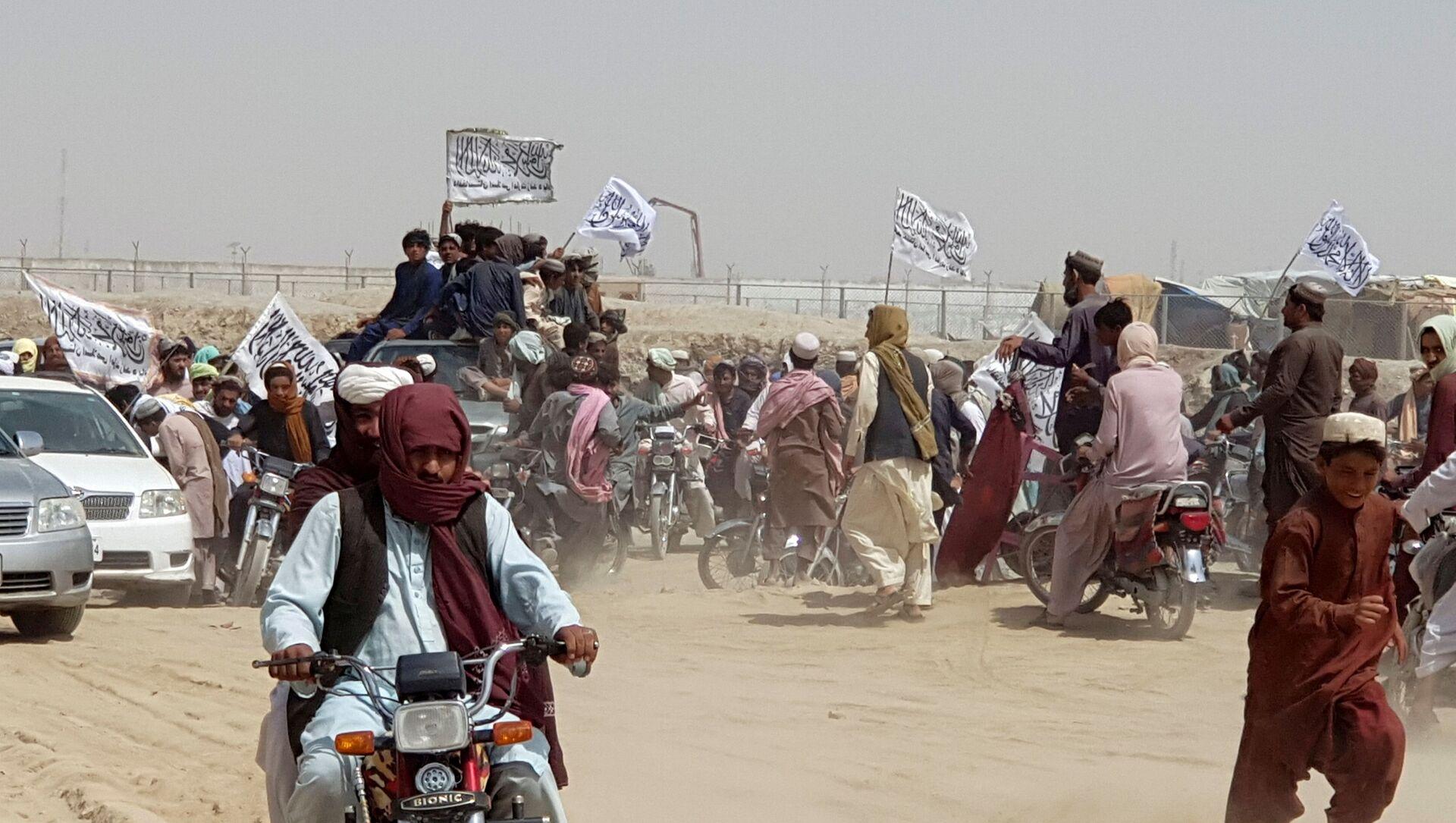 Những người trên xe, cầm cờ Taliban, tụ tập gần điểm qua Cổng Hữu nghị ở thị trấn biên giới Pakistan-Afghanistan của Chaman, Pakistan ngày 14 tháng 7 năm 2021 - Sputnik Việt Nam, 1920, 19.07.2021