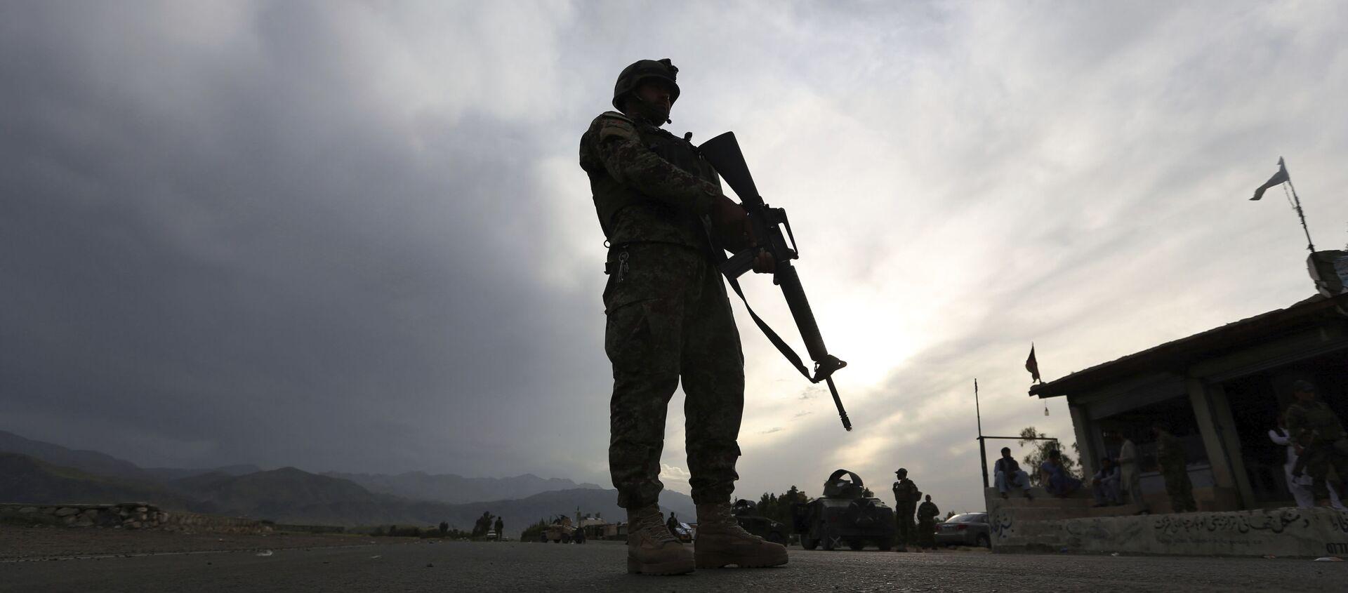 Một binh sĩ Quân đội Quốc gia Afghanistan đứng gác tại một trạm kiểm soát trên đường cao tốc Jalalabad-Kabul, Laghman - Sputnik Việt Nam, 1920, 19.09.2021