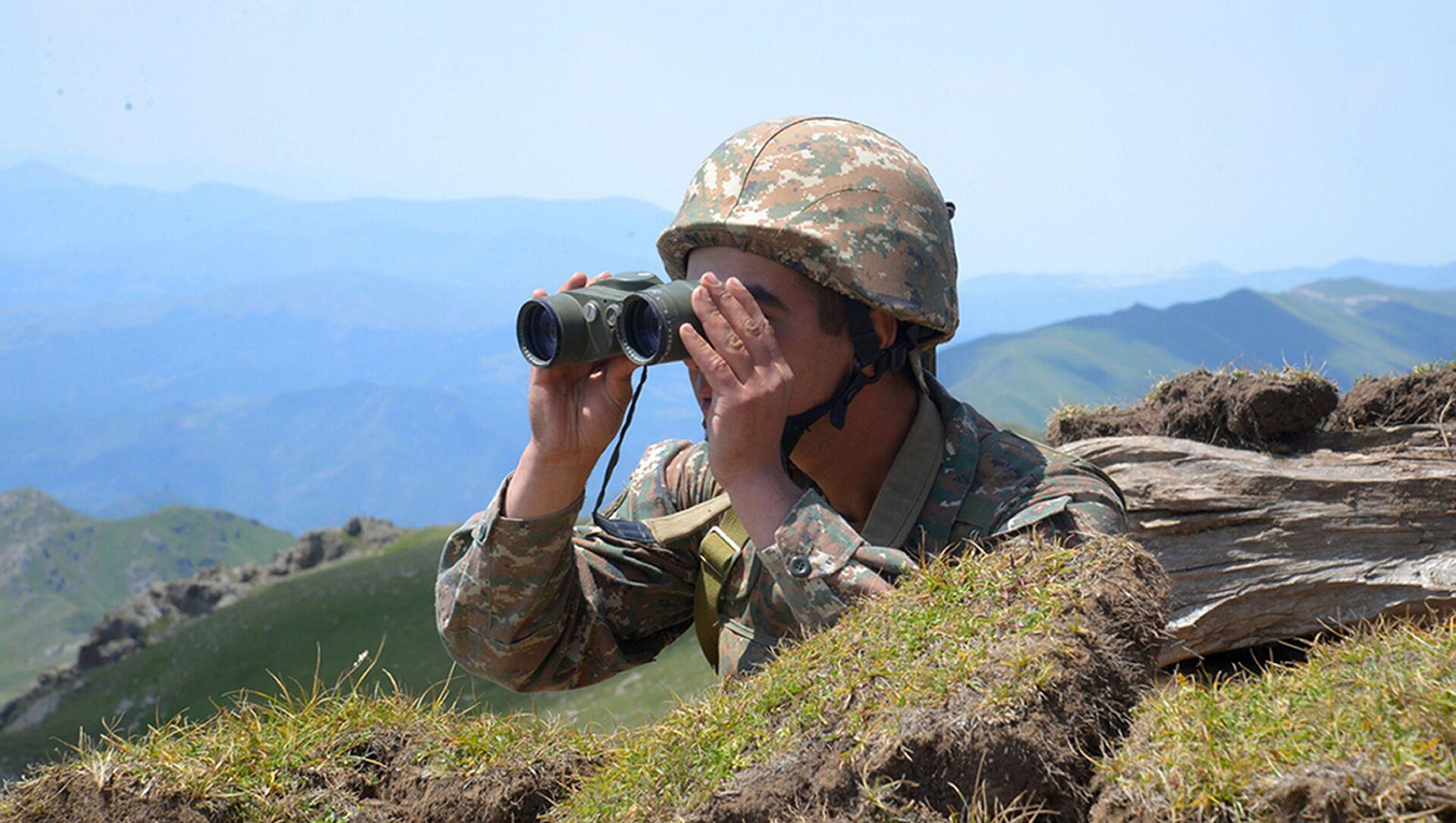 Một người lính Armenia nhìn qua ống nhòm tại vị trí của anh ta trên chiến tuyến ở vùng Tavush, Armenia - Sputnik Việt Nam, 1920, 20.07.2021