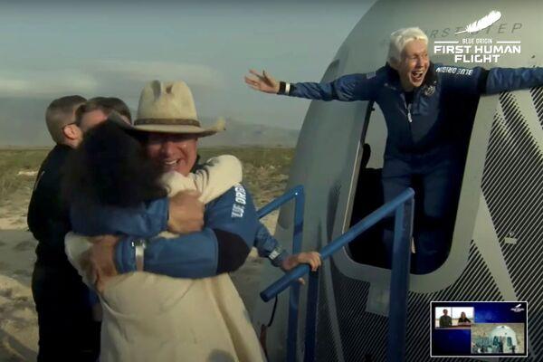 Doanh nhân Jeff Bezos và phi công Wally Funk bước ra từ khoang chứa sau khi bay trên tàu tên lửa New Shepard Blue Origin trong chuyến bay dưới quỹ đạo không người lái đầu tiên trên thế giới, Hoa Kỳ - Sputnik Việt Nam
