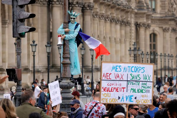 Một người biểu tình hóa trang thành Tượng Nữ thần Tự do tham gia cuộc biểu tình phản đối các biện pháp mới mà Tổng thống Pháp Emmanuel Macron công bố nhằm chống lại sự bùng phát COVID ở Paris, Pháp - Sputnik Việt Nam