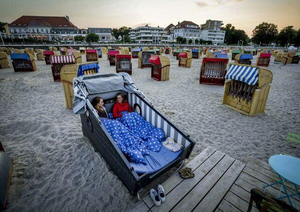 Hai cô gái chuẩn bị nghỉ đêm trên chiếc ghế tắm nắng được thiết kế đặc biệt trên bãi biển Baltic Sea ở Travemunde, Đức - Sputnik Việt Nam