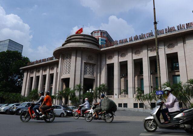 Những người đang đi xe máy qua trụ sở Ngân hàng Nhà nước Việt Nam ở trung tâm thành phố Hà Nội