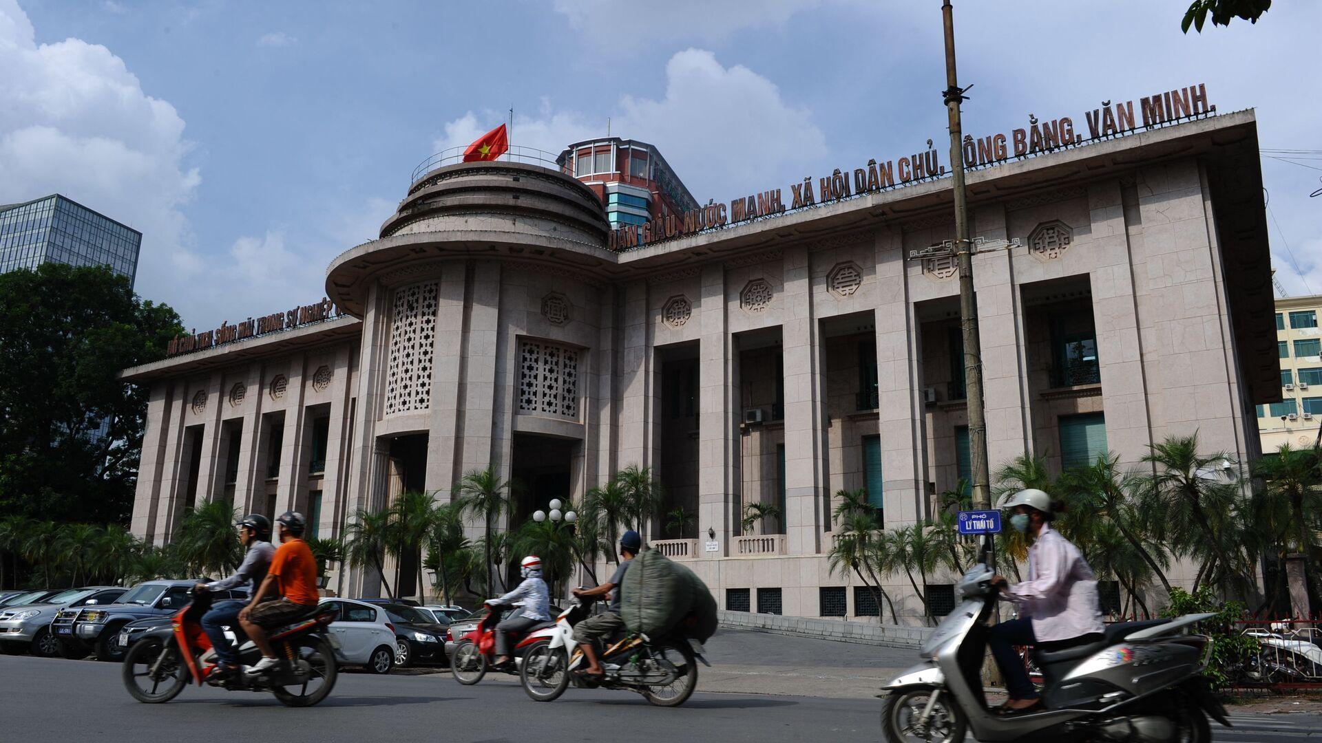 Những người đang đi xe máy qua trụ sở Ngân hàng Nhà nước Việt Nam ở trung tâm thành phố Hà Nội - Sputnik Việt Nam, 1920, 10.09.2021