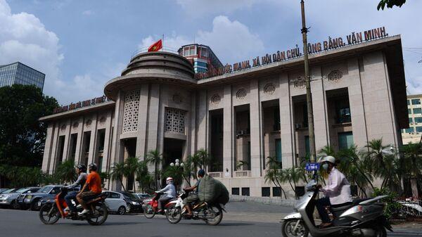 Những người đang đi xe máy qua trụ sở Ngân hàng Nhà nước Việt Nam ở trung tâm thành phố Hà Nội - Sputnik Việt Nam