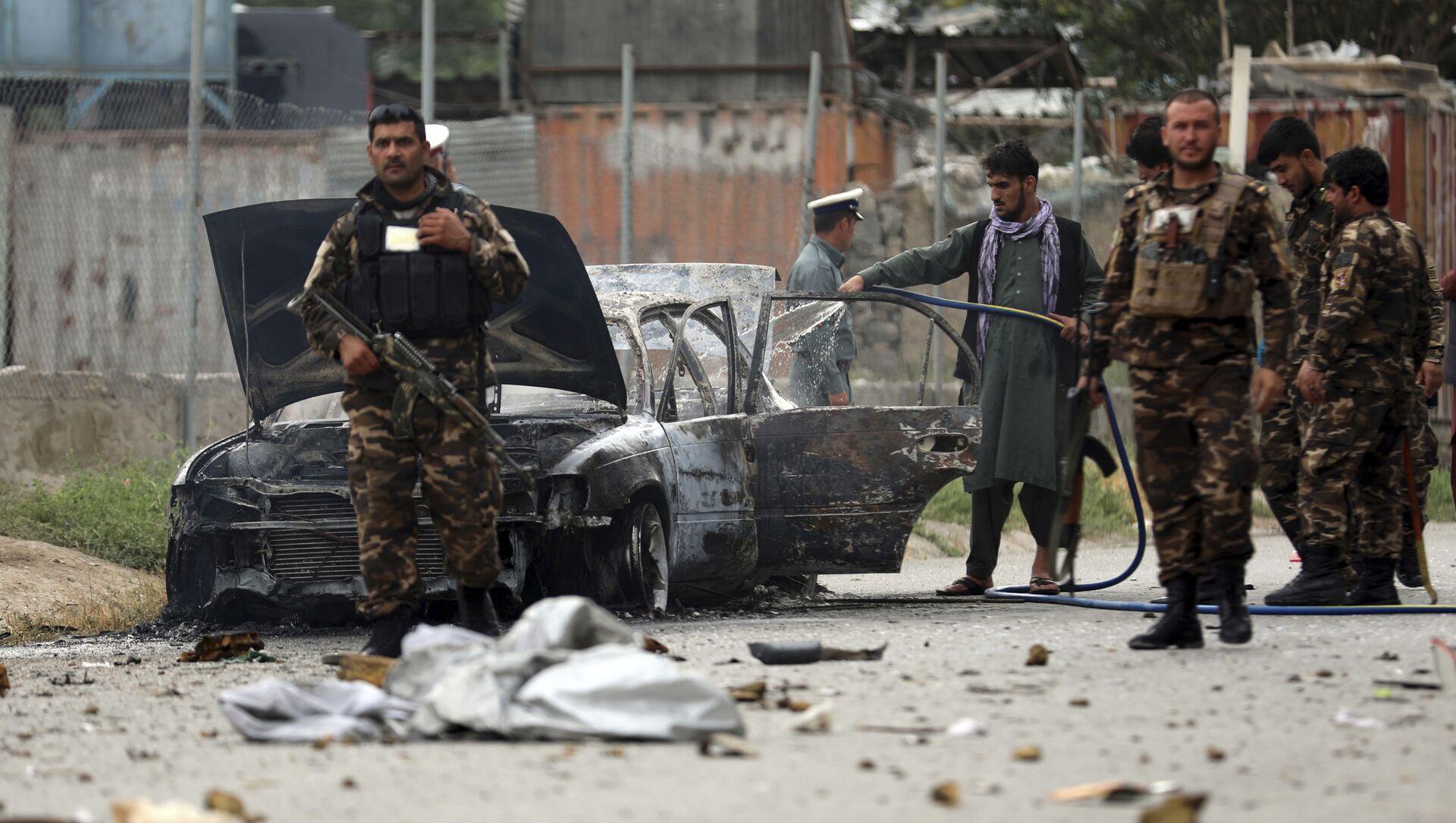 Nhân viên an ninh kiểm tra một chiếc xe bị hư hại trong cuộc pháo kích vào Kabul - Sputnik Việt Nam, 1920, 26.07.2021