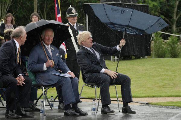 Thái tử Anh Charles và Thủ tướng Boris Johnson trú mưa trong lễ khai trương Đài tưởng niệm Cảnh sát Anh ở Olrewas, Anh - Sputnik Việt Nam
