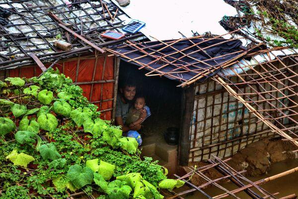 Người đàn ông tị nạn với một đứa trẻ trong nơi trú ẩn bị ngập lụt sau trận mưa lớn tại trại tị nạn của người Rohingya ở Kutupalong, Bangladesh - Sputnik Việt Nam
