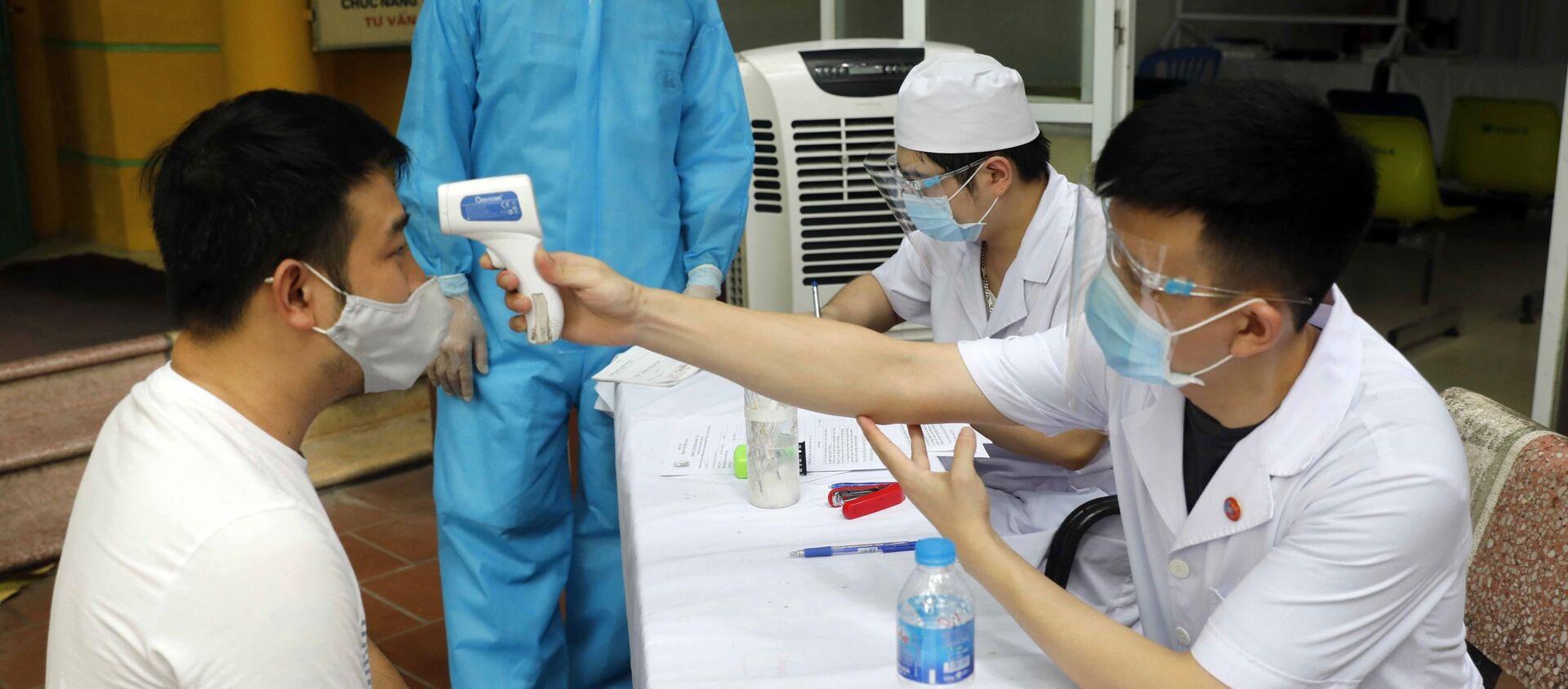 Đo thân nhiệt cho người dân đến khám, chữa bệnh tại Bệnh viện Dệt may - Sputnik Việt Nam, 1920, 08.08.2021