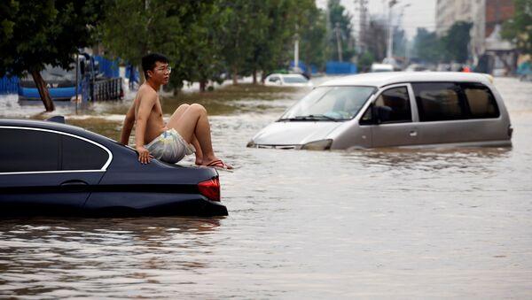 Một người đàn ông ngồi trên ô tô mắc kẹt trên con đường ngập nước sau trận mưa lớn ở Trịnh Châu, tỉnh Hà Nam, Trung Quốс - Sputnik Việt Nam