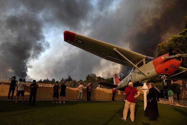 Người đứng ở cổng vào sân bay quân sự Tatoi gần Acharnes trong trận cháy rừng lớn ở phía bắc Athens - Sputnik Việt Nam
