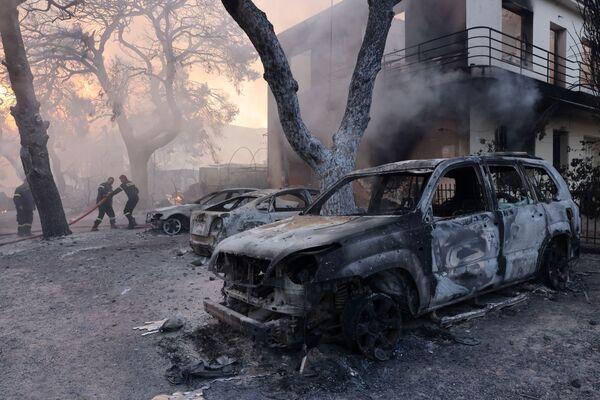 Lính cứu hỏa làm việc gần những chiếc xe bị thiêu rụi trong trận cháy rừng ở ngoại ô Varympompi, phía bắc Athens, Hy Lạp - Sputnik Việt Nam