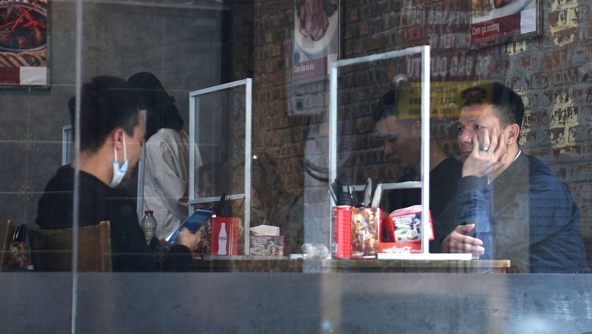 Thực khách ở Hà Nội ngồi trong nhà hàng sau tấm chắn nhựa chống coronavirus lây lan - Sputnik Việt Nam, 1920, 07.09.2021