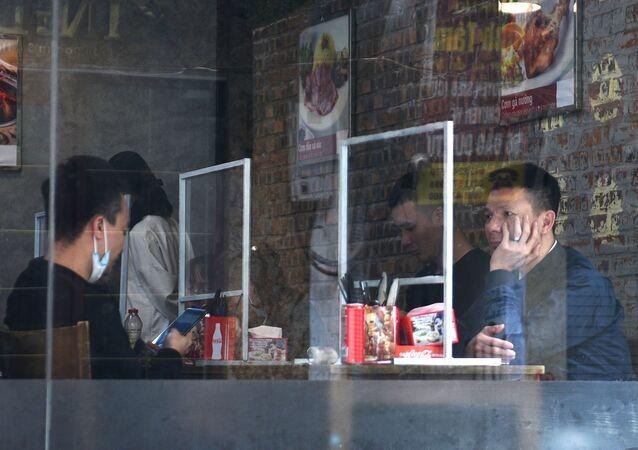 Thực khách ở Hà Nội ngồi trong nhà hàng sau tấm chắn nhựa chống coronavirus lây lan