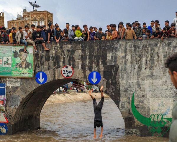 Đám thanh niên xem chàng trai nhảy từ cầu bắc qua kênh thoát nước ngập lụt ở thành phố cổ của thủ đô Yemen - Sputnik Việt Nam