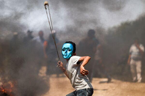 Đứa trẻ Palestine đeo mặt nạ ném đá trong cuộc đụng độ với lực lượng Israel tại làng Beita ở phía bắc Bờ Tây bị chiếm đóng - Sputnik Việt Nam