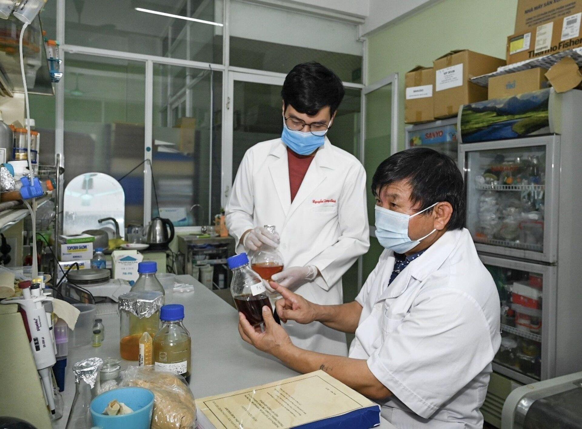 PGS.TS.Nghiên cứu viên cao cấp Lê Quang Huấn (bên phải) và cộng sự nghiên cứu thuốc điều trị Covid-19 - Sputnik Việt Nam, 1920, 05.10.2021