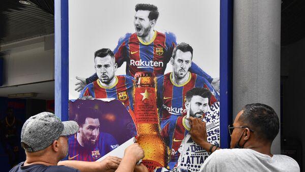 Công nhân gỡ bỏ áp phích in hình tiền đạo người Argentina Lionel Messi của Barcelona tại sân vận động Camp Nou ở Barcelona - Sputnik Việt Nam