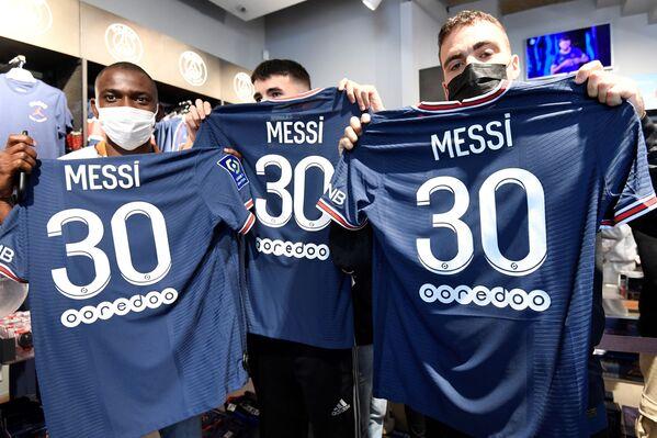 Người hâm mộ tạo dáng với áo phông manh hình cầu thủ bóng đá Argentina Lionel Messi của PSG ở Paris - Sputnik Việt Nam