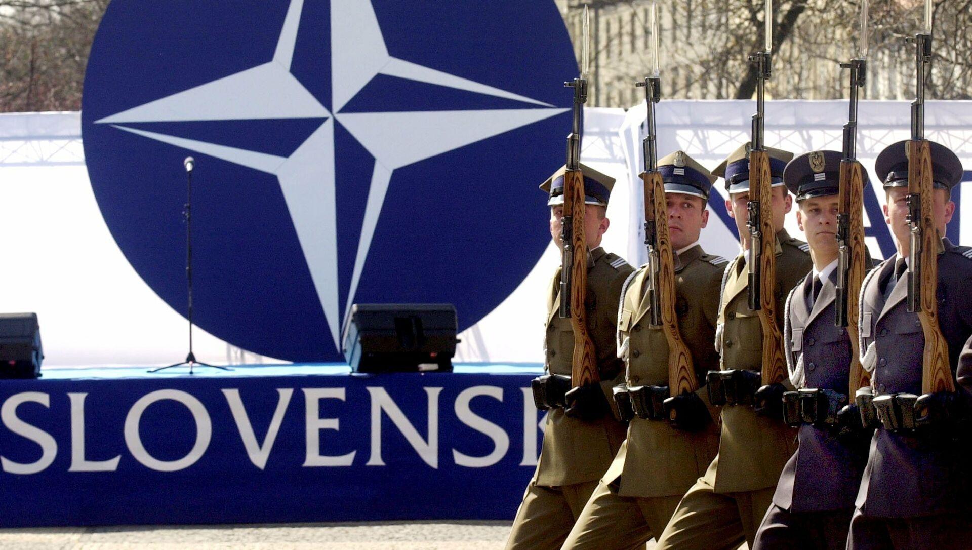 Các thành viên của đội bảo vệ danh dự giơ vũ khí trước logo NATO trong buổi lễ đánh dấu các nước gia nhập liên minh quân sự vào thứ Sáu, ngày 2 tháng 4 năm 2004 tại Bratislava - Sputnik Việt Nam, 1920, 13.08.2021