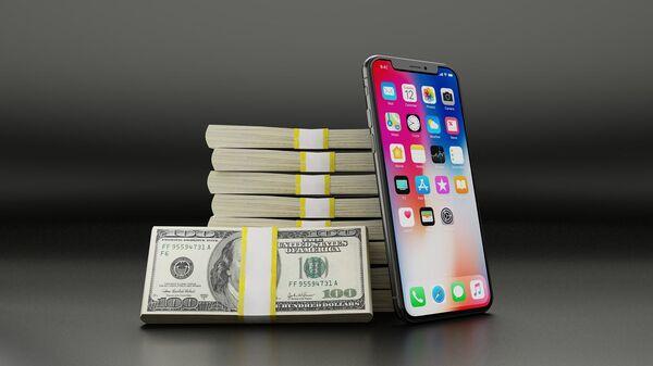 Một chiếc iPhone đặt bên cạnh những gói tiền giấy đô la Mỹ - Sputnik Việt Nam