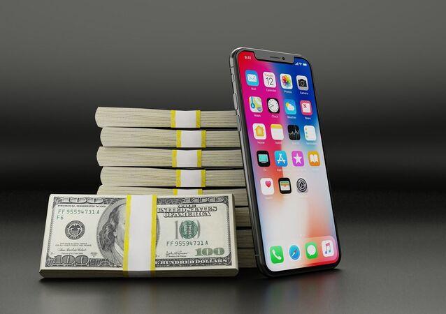 Một chiếc iPhone đặt bên cạnh những gói tiền giấy đô la Mỹ