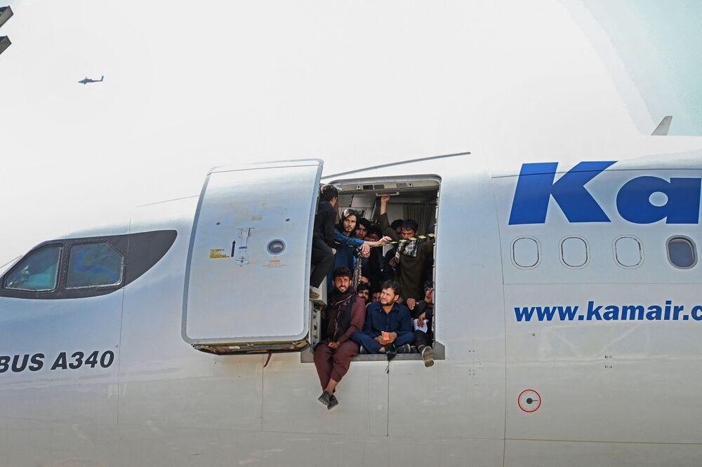 Người dân Afghan ngồi ở cửa máy bay tại phi trường Kabul