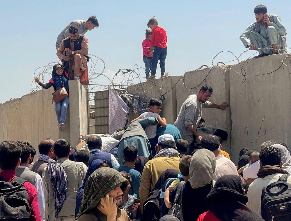Một người đàn ông cố đẩy cô bé lên trên ở sân bay Kabul