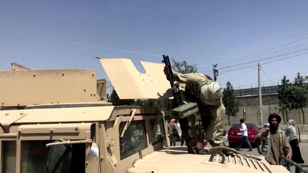 Chiến binh Taliban* với súng trên xe bọc thép gần sân bay Kabul