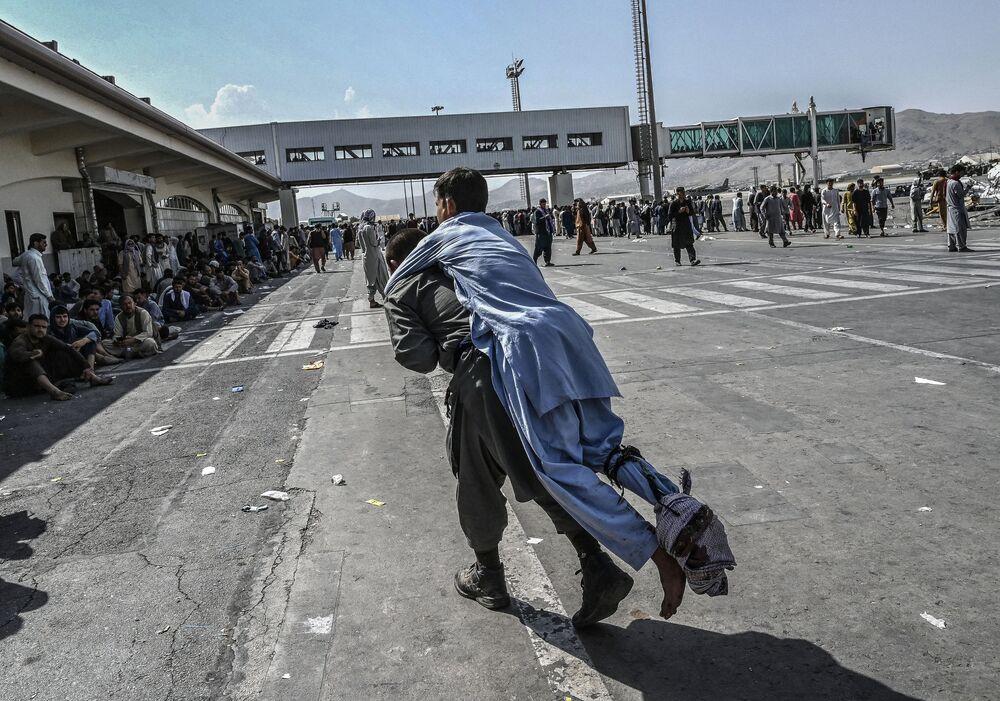 Tình nguyện viên với một người Afghan bị thương ở sân bay Kabul