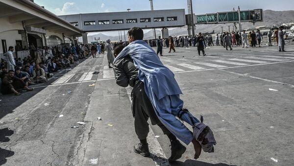Tình nguyện viên với một người Afghan bị thương ở sân bay Kabul - Sputnik Việt Nam