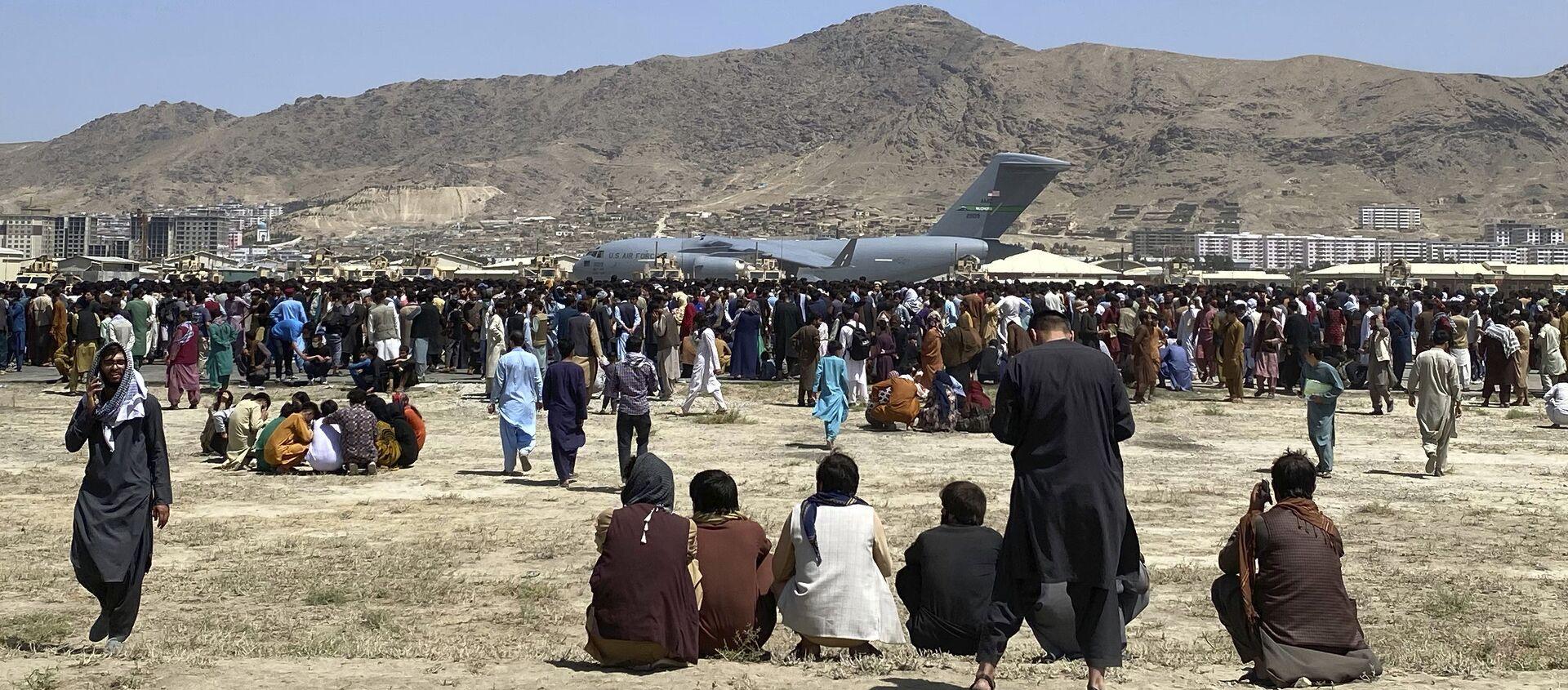 Hàng trăm người tập trung gần một chiếc máy bay vận tải C-17 của Không quân Hoa Kỳ ở vành đai sân bay quốc tế ở Kabul, Afghanistan, Thứ Hai, ngày 16 tháng 8 năm 2021 - Sputnik Việt Nam, 1920, 17.08.2021