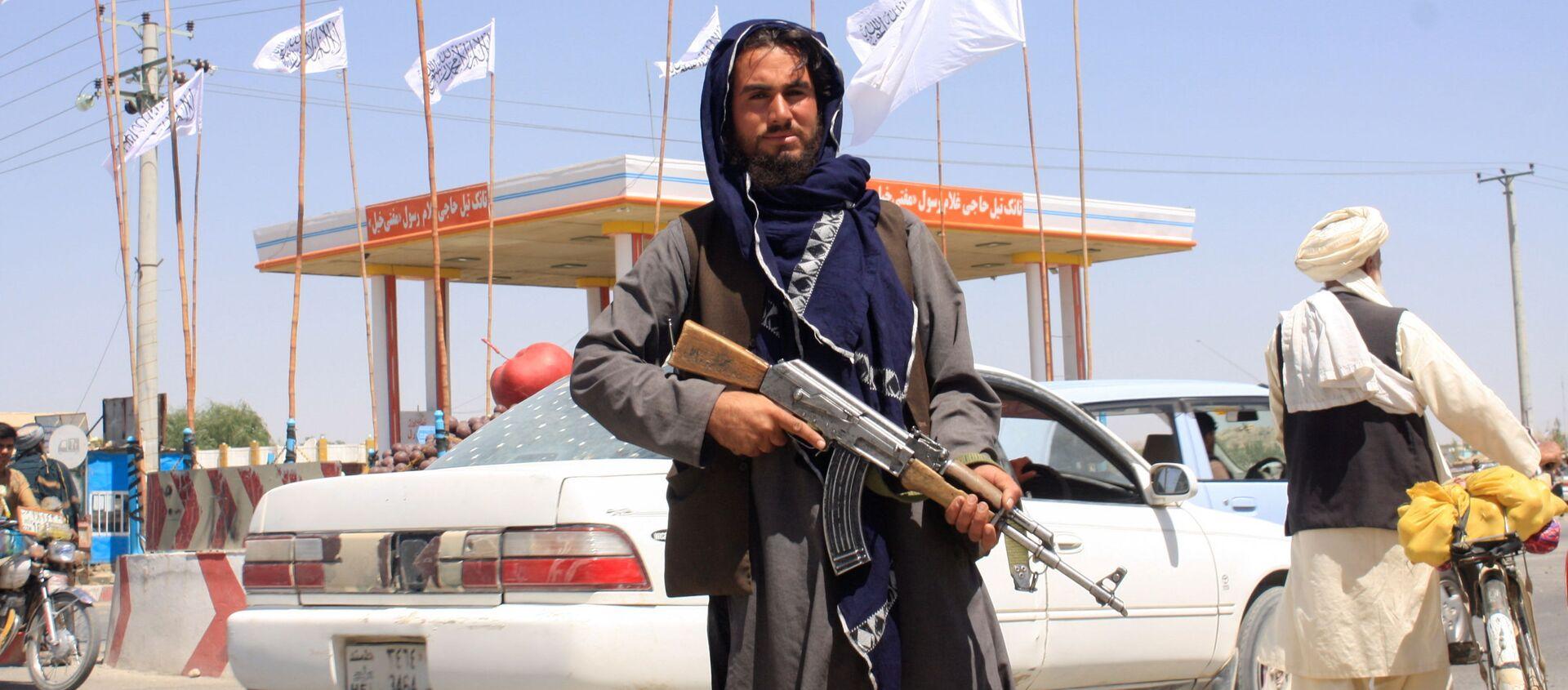 Một chiến binh Taliban đứng nhìn khi anh ta đứng tại thành phố Ghazni, Afghanistan ngày 14 tháng 8 năm 2021. - Sputnik Việt Nam, 1920, 17.08.2021